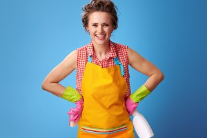 happy woman with kitchen sponge and cleaning detergent on blue