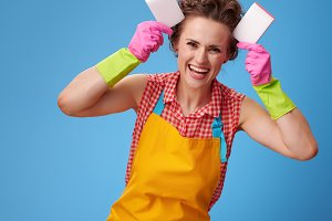 happy young housewife making ears with kitchen sponges on blue