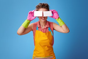 smiling woman holding kitchen sponges in front of face on blue