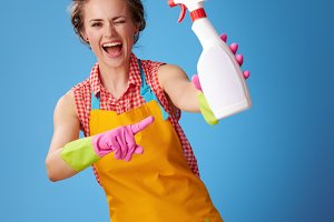 happy woman winking and pointing at bottle of detergent on blue