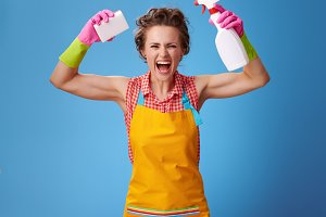 housewife with kitchen sponge and a bottle of detergent showing biceps