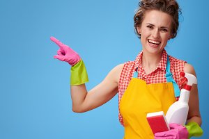 woman with kitchen sponge and a bottle of detergent pointing at something
