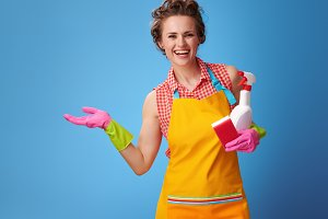 woman with kitchen sponge and a bottle of detergent presenting something on empty palm