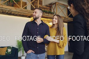 Confident housing agent is showing spacious modern house with beautiful interior to happy young couple, people are smiling and talking looking around.