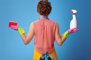 woman showing kitchen sponge and bottle of detergent on blue