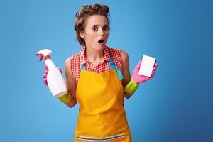 woman with kitchen sponge and bottle of detergent on blue