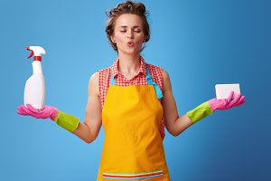 woman with kitchen sponge and a bottle of detergent doing yoga