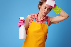 housewife with kitchen sponge and bottle of detergent on blue