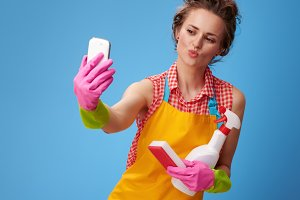 woman with kitchen sponge and a bottle of detergent taking selfie with phone
