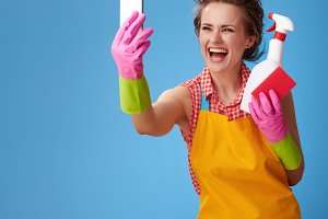 woman with kitchen sponge and a bottle of detergent taking selfie with mobile phone
