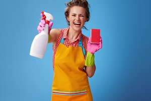 woman with kitchen sponge showing bottle of detergent on blue