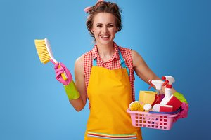 housewife with basket of cleaning supplies and brush on blue