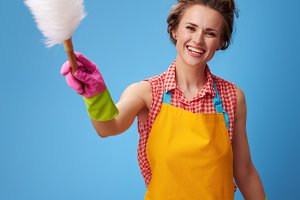 smiling young woman in yellow apron on blue using duster brush