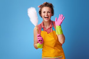 smiling young housewife with duster brush on blue
