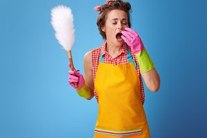 modern housewife with duster brush sneezing on blue