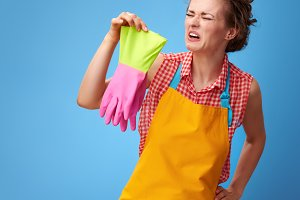 sad young housewife sniffing rubber gloves on blue