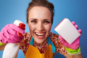 happy woman using kitchen sponge and cleaning detergent on blue