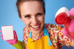housewife with kitchen sponge using cleaning detergent on blue