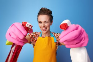 happy woman using bottles of cleaning detergent as guns on blue