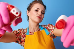 housewife using bottles of cleaning detergent as guns on blue