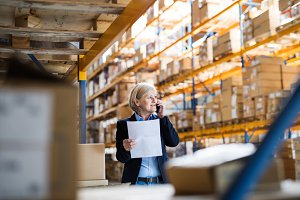 Senior woman warehouse manager or supervisor with smartphone making a phone call.