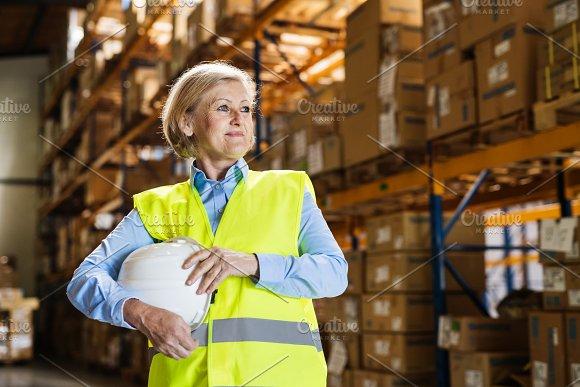Senior woman warehouse manager or supervisor holding white helmet.