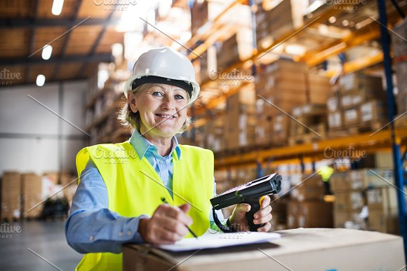 Senior warehouse woman worker with barcode scanner.