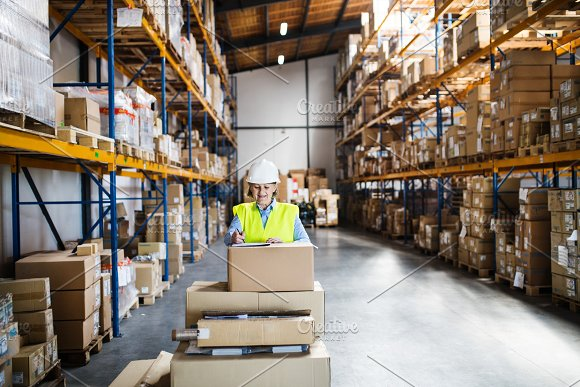 A senior woman warehouse worker or supervisor controlling boxes. in Graphics