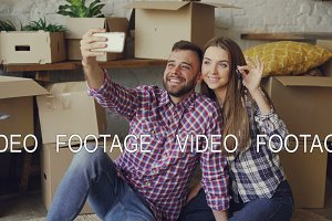 Happy couple is taking selfie with house keys after purchasing new apartment. Young people are posing and kissing looking at smartphone camera with boxes in background.