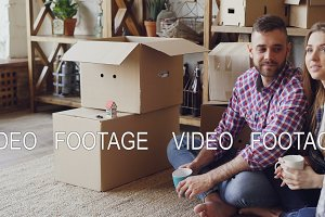 Handsome man and attractive woman are sitting on floor in new house and planning interior of their new home holding mugs. Carton boxes, shelves and window in background.