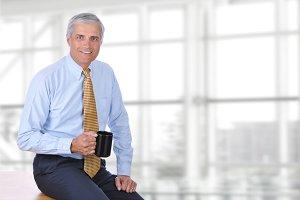 Mature Businessman Sitting on Desk