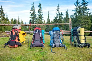 Four backpacks and hiking poles