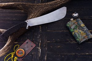 A machete of a hunter. Camouflaged jar. Compass for orientation.