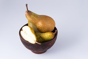 Still life of pears. Sliced pear in a deep plate.