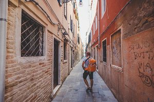 tourist with an orange backpack and bandana walks along narrow street in Europe. Italy Venice in summer. The facade of old houses without people and crowds of tourists. Unpublished places in Venice