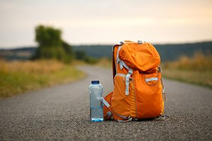 a backpack for an orange camera and a bottle of water on an asphalt road in a field