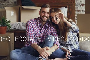 Portrait of happy young couple sitting together in new flat, holding keys and looking at camera. Nice loft style interior, carton boxes and bed are visible.