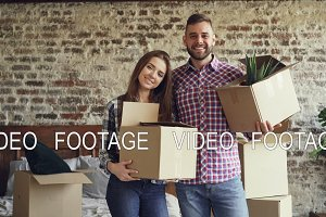 Portrait of happy young couple standing in new house, holding carton boxes, smiling and looking at camera. Family, relationship and relocation concept.