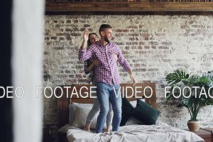 Funny young couple is dancing on bed having fun in loft style bedroom and laughing. Happy people, modern lifestyle and romantic relationship concept.