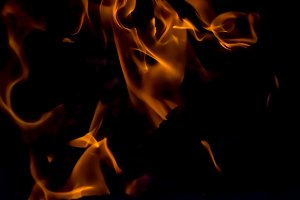 A beautiful horizontal texture of a burning fire on a black background with sparks