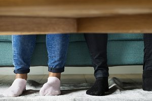 Feet sticking out under a sofa table