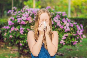 Pollen allergy concept. Young woman is going to sneeze. Flowering trees in background