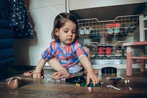 Baby girl playing with hair clips sitting in the floor
