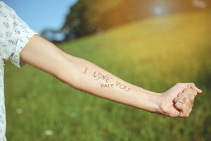 Male arm with text -I hate you- written in skin