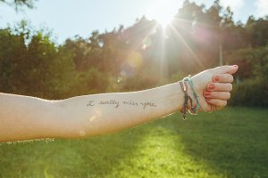 Female arm with text -I really miss you- written in skin