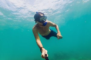 A young caucasian snorkeling man under water selfie Thailand