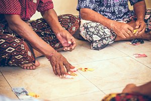 Group of balinese men playing cards sitting on the floor. Bali island.