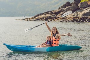 Mother and son kayaking at tropical ocean.