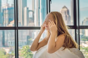 Woman wakes up in the morning in an apartment in the downtown area with a view of the skyscrapers. Life in the noise of the big city concept. Not enough sleep