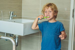 Little blond boy learning brushing his teeth in domestic bath. Kid learning how to stay healthy. Health care concept